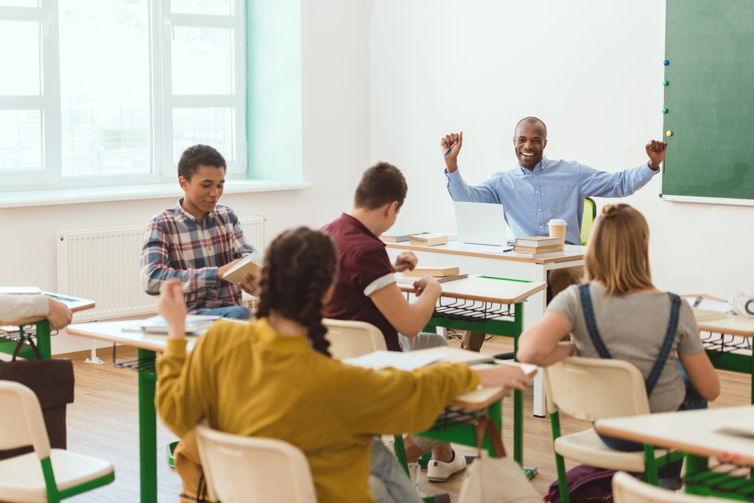Multicultural group of teenage schoolchildren and smiling african american teacher with raising arms