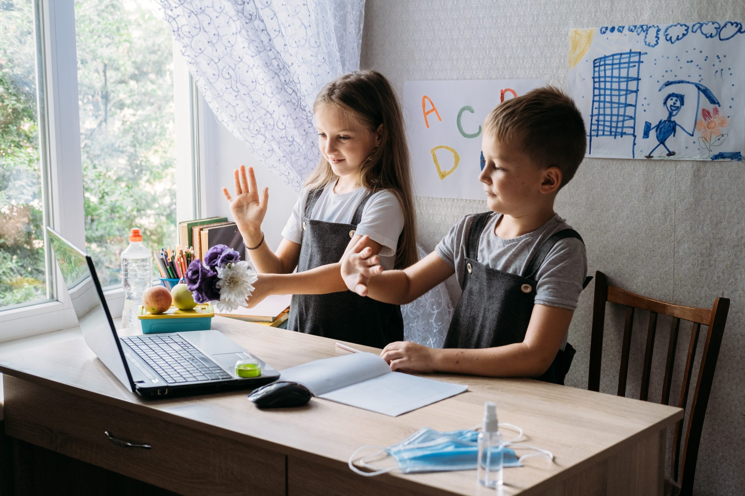 Schoolkids boy and girl using laptop for online study during homeschooling at home. Homeschooling, online study, home quarantine online learning education corona virus or online technology